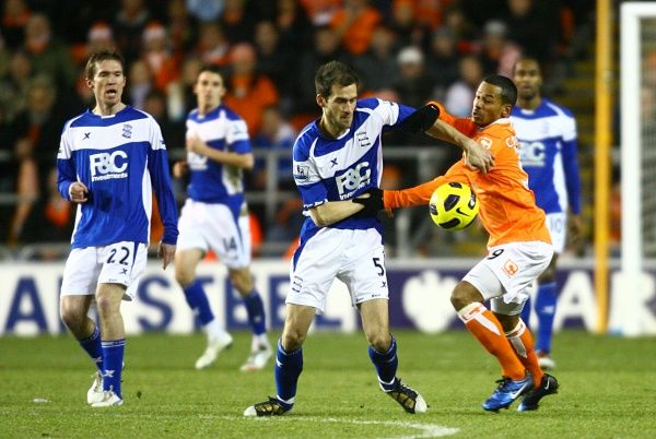 Birmingham City's Roger Johnson (centre) and Blackpool's Dudley Campbell (right) battle for the ball