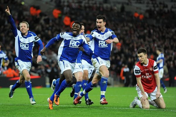 Arsenal's Laurent Koscielny (right) is left dejected as Birmingham City's Obafemi Martins (centre) celebrates wildly with team-mates after scoring their second goal of the game