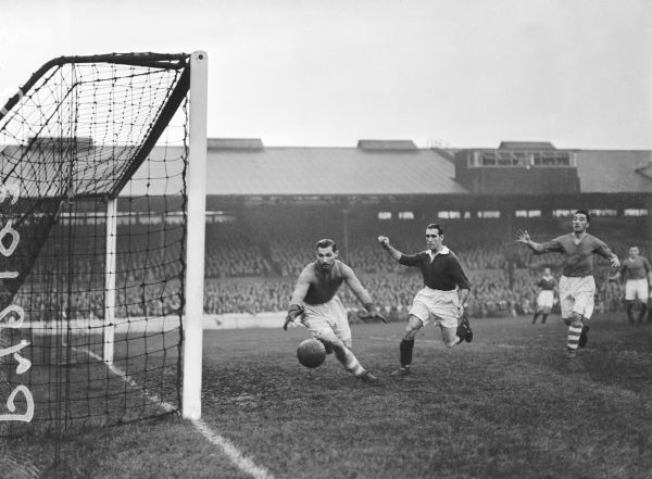 Birmingham City goalkeeper Gil Merrick (l) scrambles after the ball as it bounces towards the corner of the net, watched by Chelsea's Len Goulden (c)